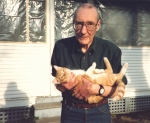 William S. Burroughs and his cat Ginger in the backyard of his home in Lawrence, Kansas